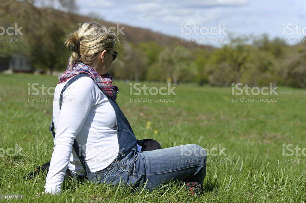 Pregnant woman sitting on grass royalty-free stock photo