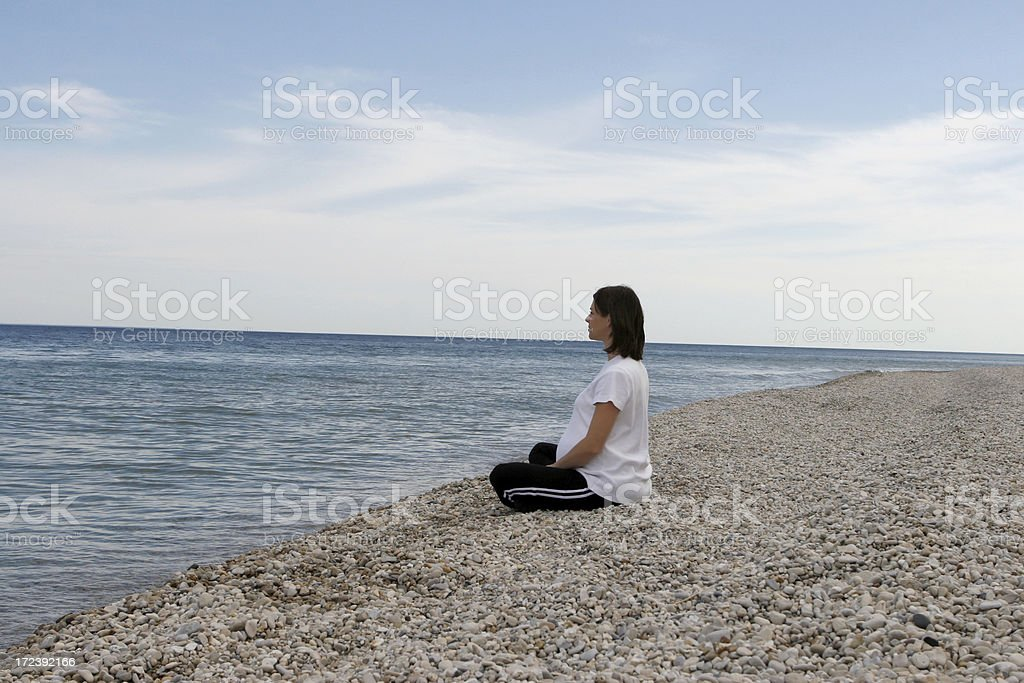 pregnant woman sitting on rocky beach royalty-free stock photo