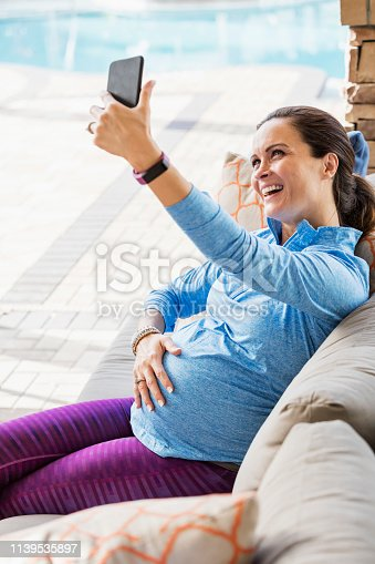 A pregnant mid adult woman in her 30s relaxing outdoors, sitting on a sofa on a patio, laughing as she takes a selfie, hand on her abdomen, feeling the baby kick.