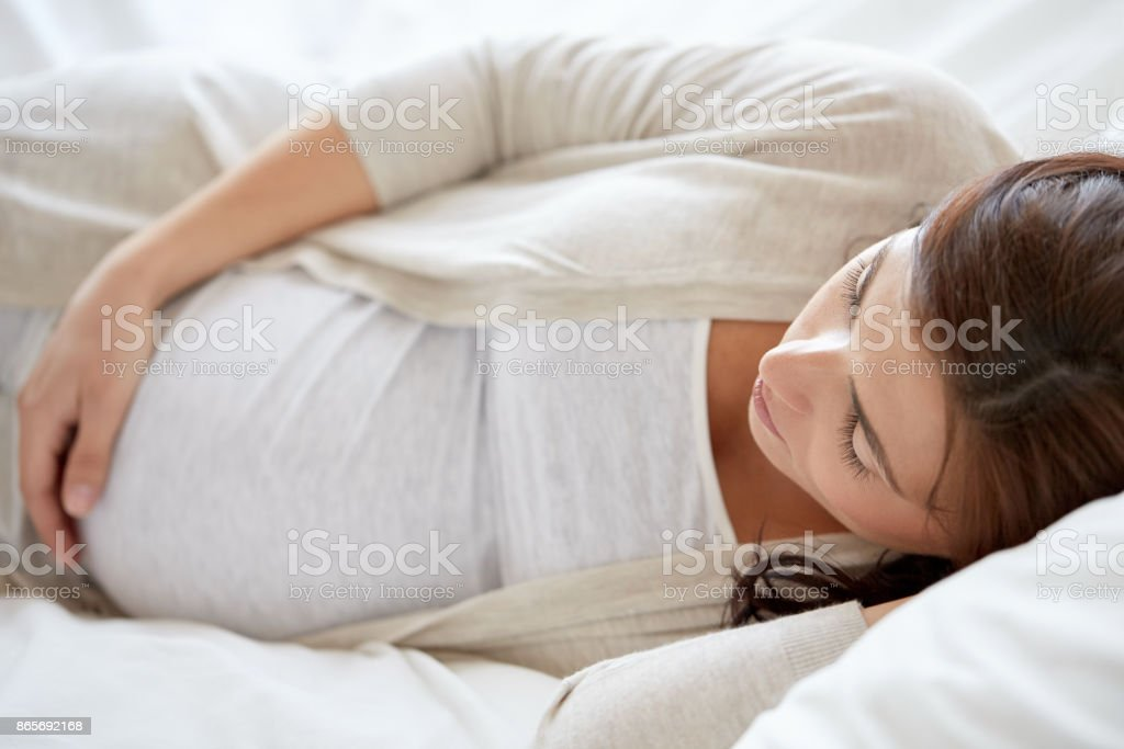 pregnant woman sleeping in bed at home stock photo