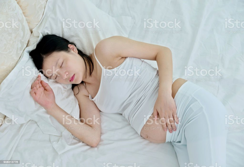 Pregnant woman sleeping in bed stock photo