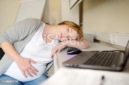Pregnant woman sleeping near laptop at her working place in office. Medical insurance childbearing. Maternity. Pregnancy and work. Health care and medicine.