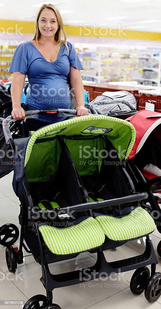 Pregnant woman smiles, selecting a stroller for twins stock photo