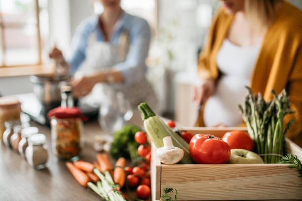 Pregnant woman spending time with her friend in the kitchen stock photo