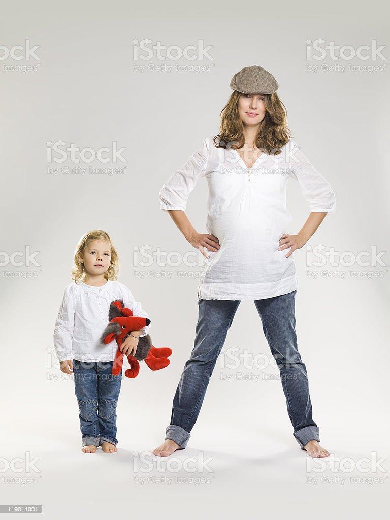 Беременная женщина стоя с дочерью стоковое фото