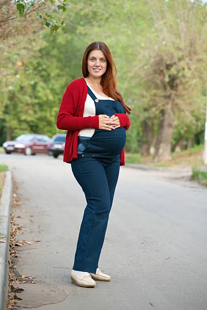 schwangere frau steht auf street - latzhose für schwangere stock-fotos und bilder