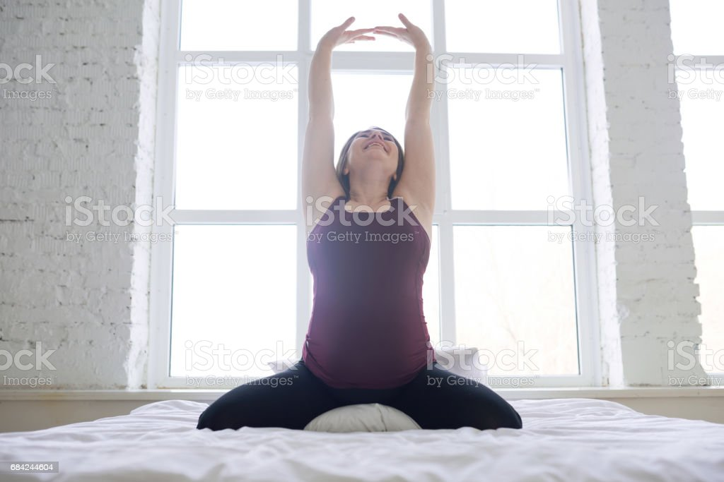 Pregnant woman stretching in bed royalty-free stock photo