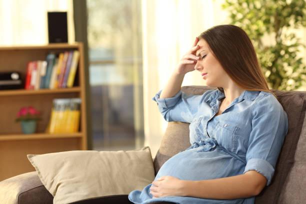 Pregnant woman suffering headache stock photo