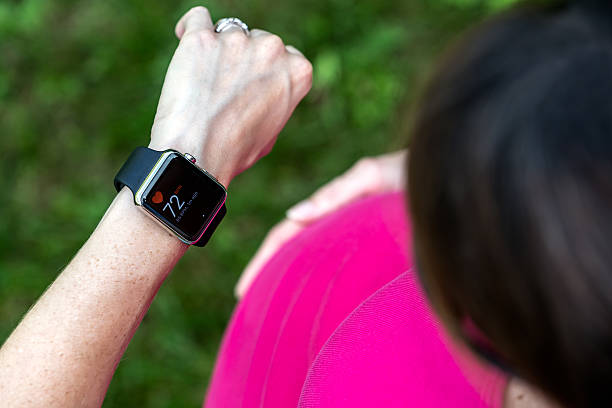 Pregnant Woman Taking Pulse on Apple Watch stock photo