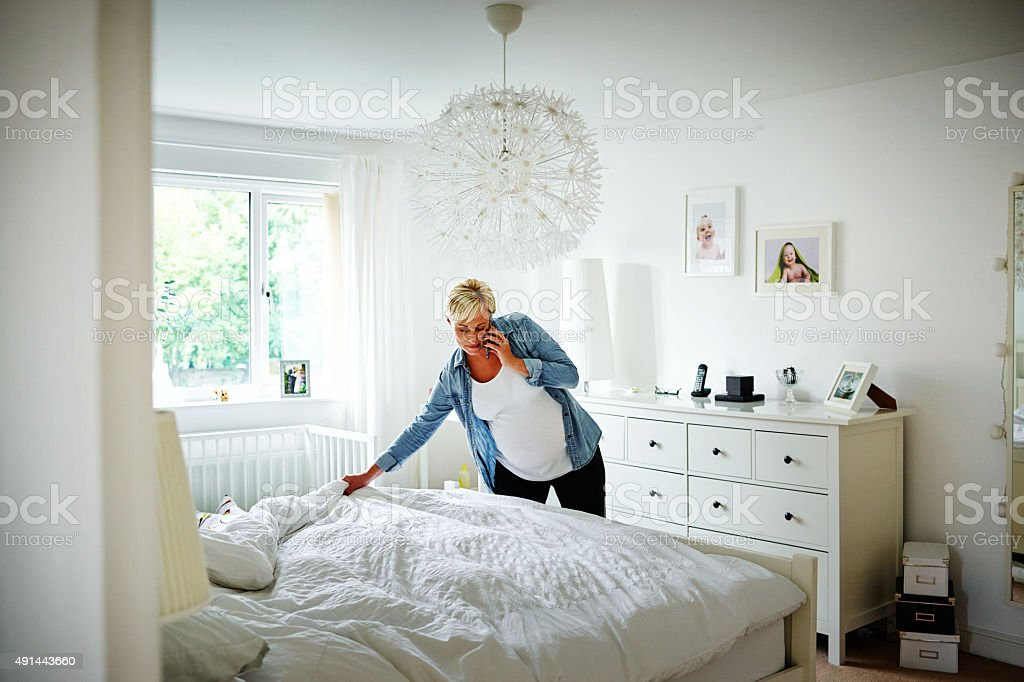 Pregnant woman talking on mobile phone and making bed stock photo