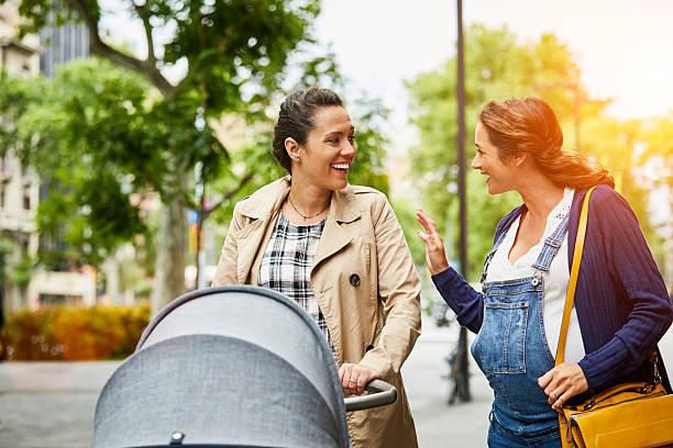 Pregnant woman talking to friend on sidewalk - foto de stock