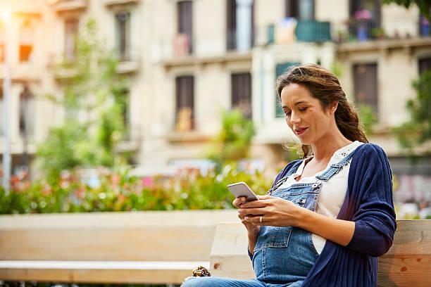 pregnant woman text messaging in park - latzhose für schwangere stock-fotos und bilder