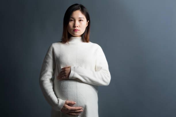 Pregnant woman touching abdomen over grey background stock photo