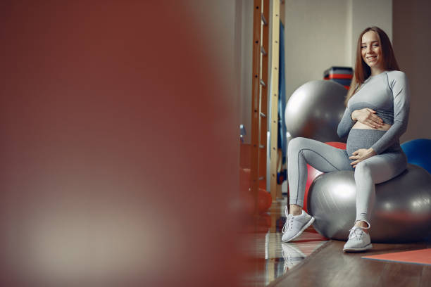 Pregnant woman training in a gym stock photo