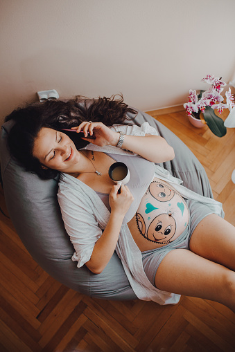 istock A pregnant woman uses the phone and takes a selfie 1255216851