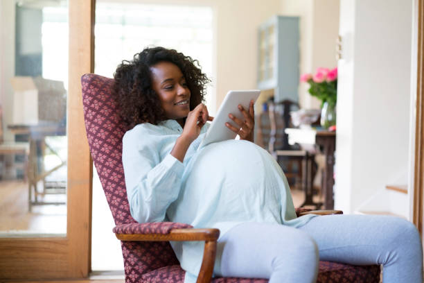 Pregnant woman using digital tablet at home stock photo