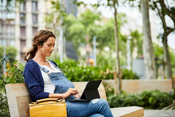 pregnant woman using laptop while sitting on bench - latzhose für schwangere stock-fotos und bilder