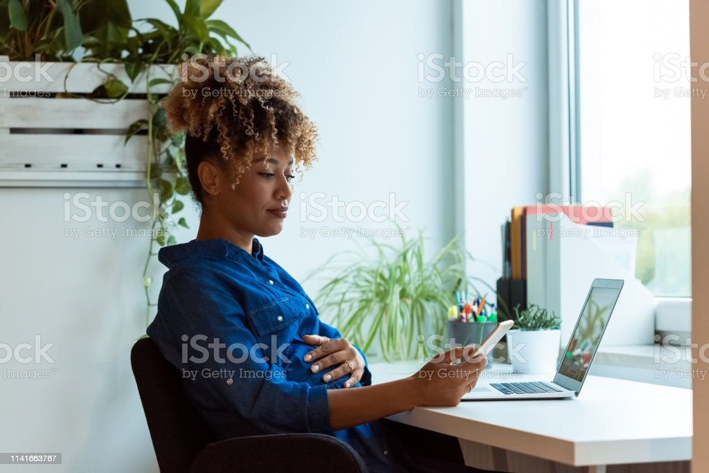 Pregnant woman using mobile phone in new office Pregnant businesswoman with hand on stomach using mobile phone. Female expertise is sitting in new office. She is wearing denim. 35-39 Years Stock Photo