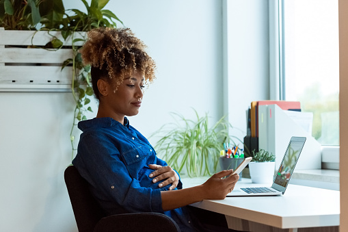 Pregnant Woman Using Mobile Phone In New Office Stock Photo - Download Image Now