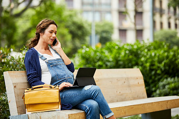pregnant woman using technologies on bench - latzhose für schwangere stock-fotos und bilder