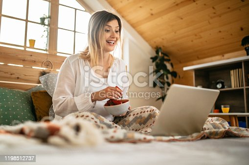 Young pregnant woman working on laptop from bed, in her bedroom