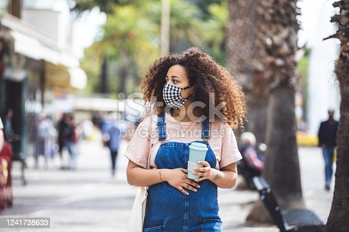 Pregnant woman walking in the city in a sunny day protecting herself with a cloth face mask in Italy during Covid-19 coronavirus pandemic