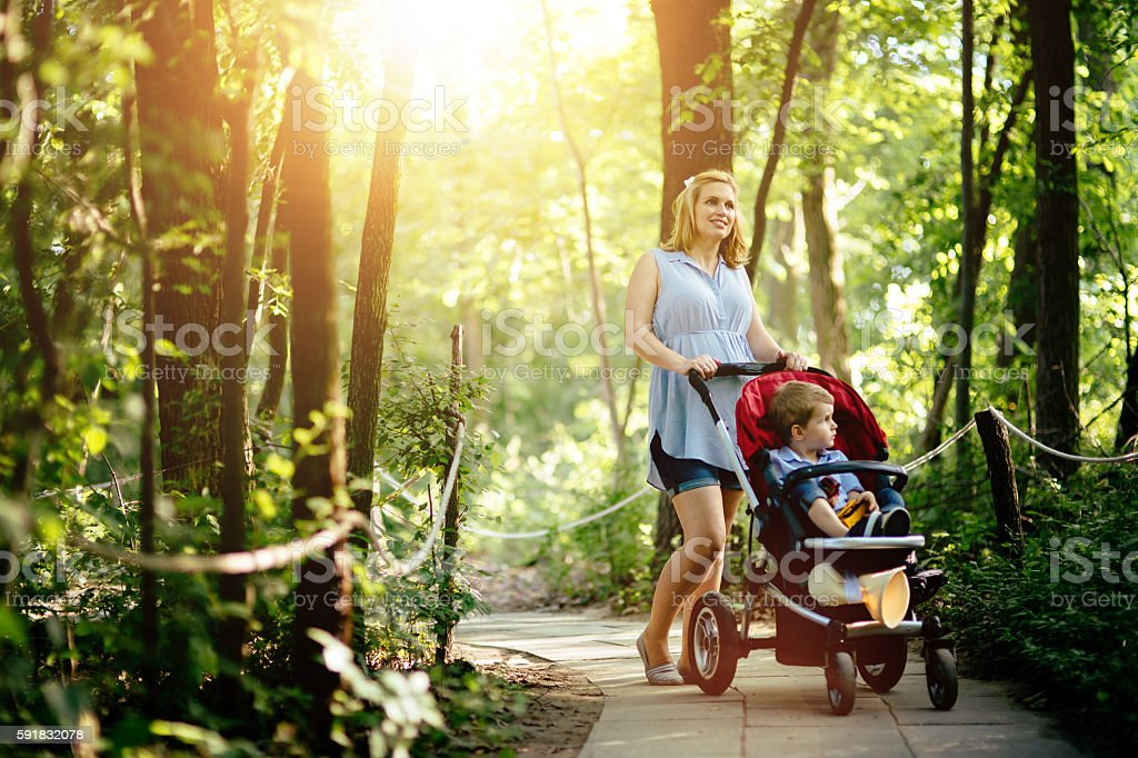 Pregnant woman walking with child in nature stock photo
