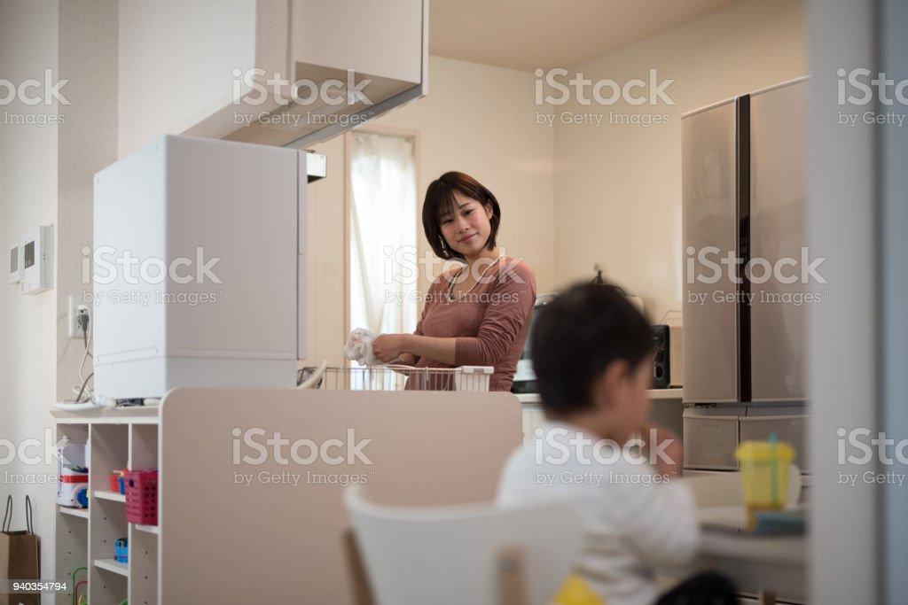 妊娠中の女性が台所で皿と昼食を食べて彼女の子供を洗浄 ストックフォト