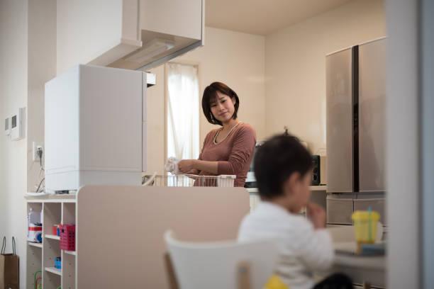 妊娠中の女性が台所で皿と昼食を食べて彼女の子供を洗浄 - 家事 ストックフォトと画像