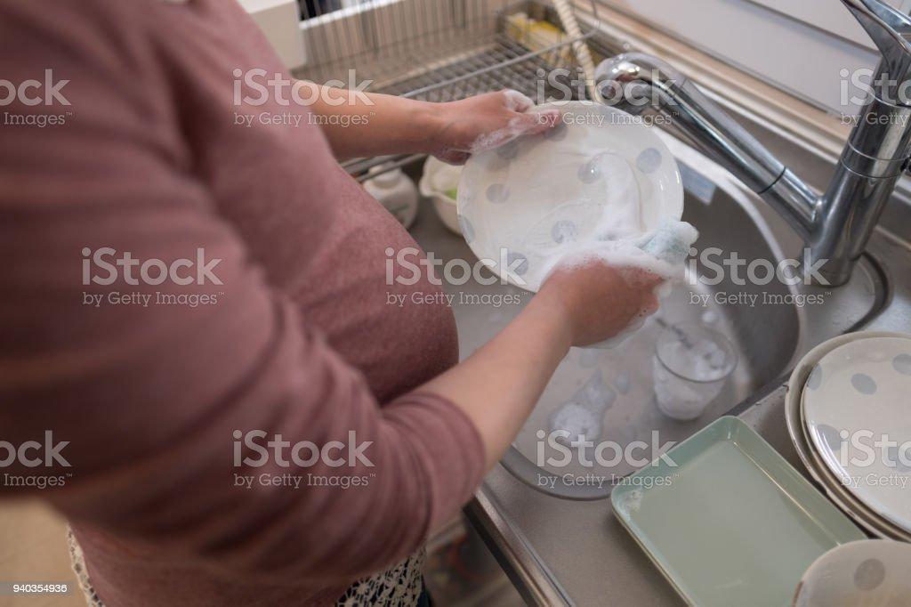 Prato de lavar roupa de mulher grávida na cozinha - foto de acervo