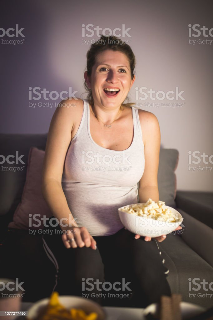 Pregnant woman watching a comedy and laughing stock photo