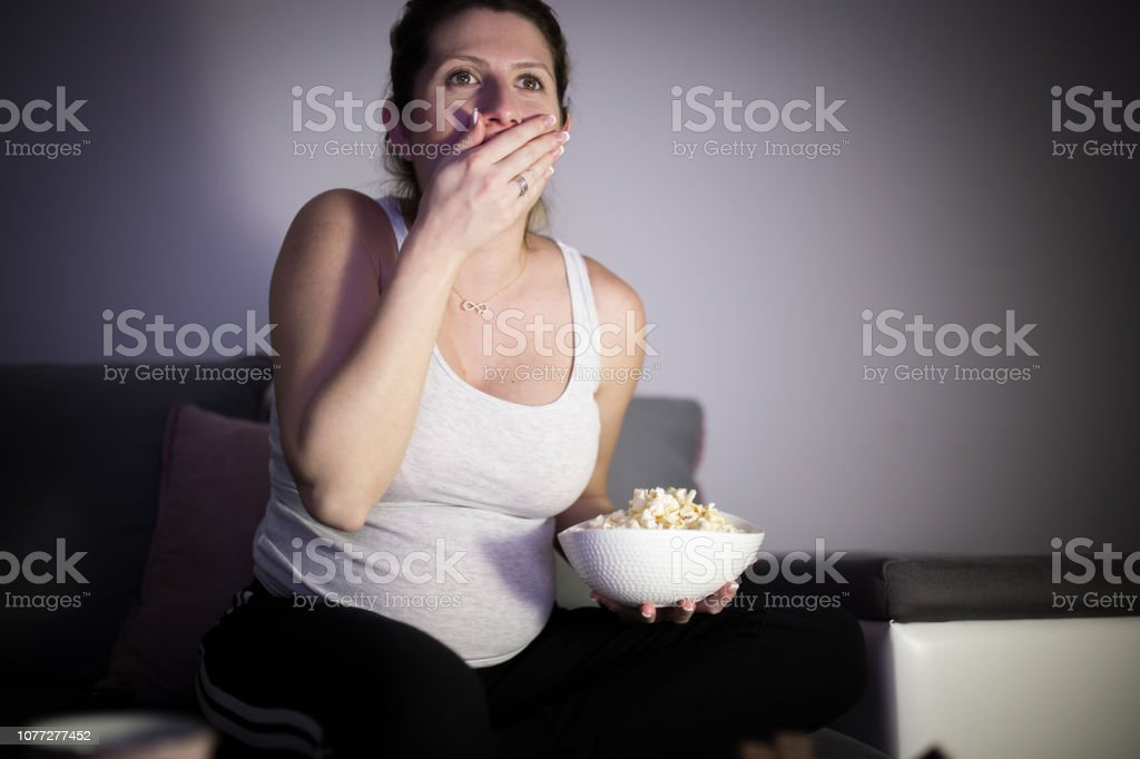 Pregnant woman watching an exciting movie stock photo
