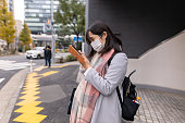 Pregnant woman wearing mask and using smart phone on street