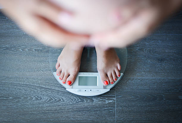 pregnant woman weighing herself on a bathroom scale - mom spying stock photos and pictures