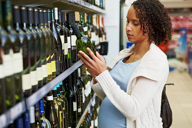 Pregnant woman with a bottle of wine at super market stock photo