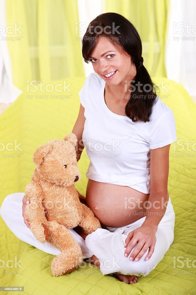 Pregnant woman with a cute teddy bear royalty-free stock photo