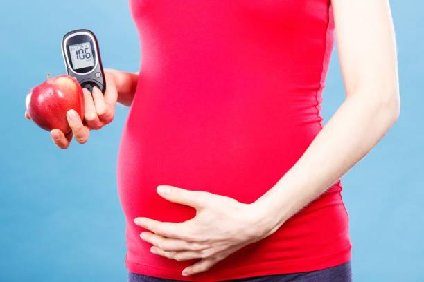 Schwangere Frau mit Apfel und Glucose Meter mit guten Ergebnis Blutzuckerspiegel, Diabetes und Ernährung während der Schwangerschaft – Foto
