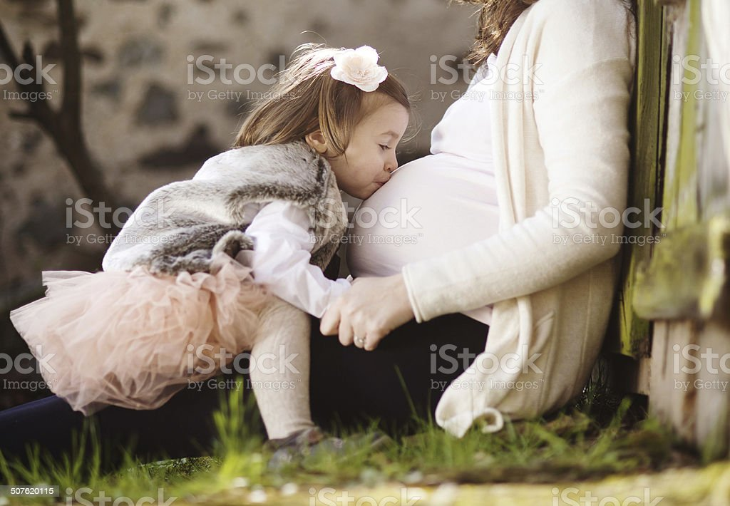 Pregnant woman with daughter stock photo