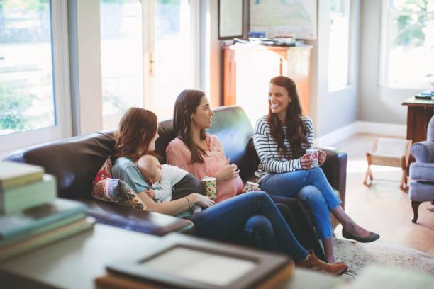 Mujer embarazada con el niño en el sofá y amigos - foto de stock