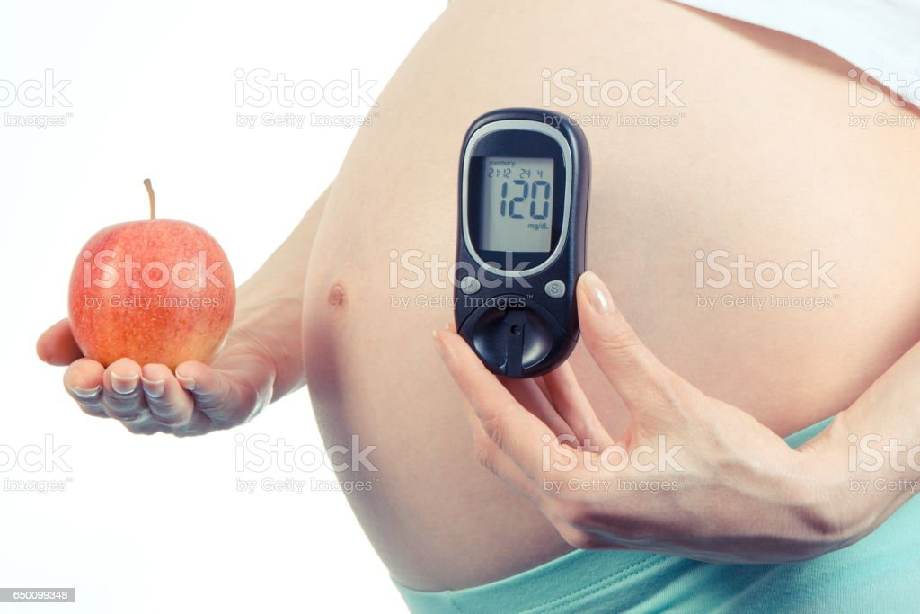 Pregnant woman with glucometer and apple, diabetes and healthy nutrition during pregnancy stock photo