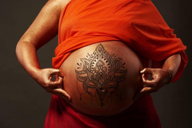 schwangere frau mit goldenen körperkunst und mandala im buddha-look - buddhist tattoos stock-fotos und bilder