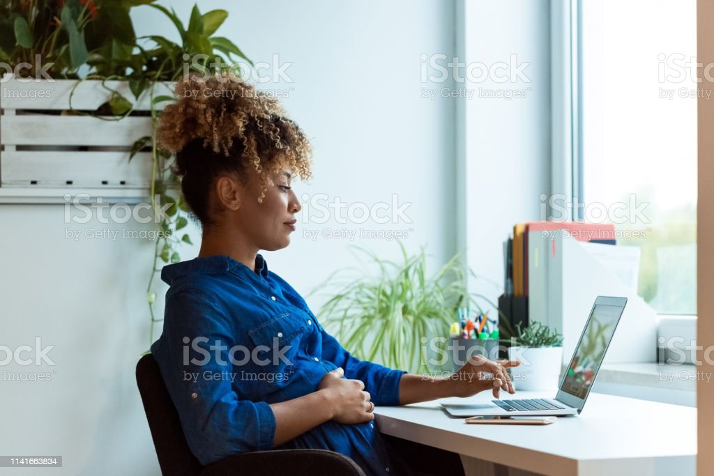 Pregnant woman with hand on belly using laptop Pregnant businesswoman with hand on stomach working at desk. Female professional is wearing business casuals. She is using laptop in office. 35-39 Years Stock Photo