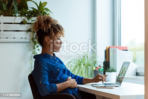Pregnant businesswoman with hand on stomach working at desk. Female professional is wearing business casuals. She is using laptop in office.