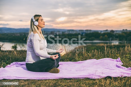 Beautiful pregnant woman with headphones enjoys meditating outdoor.Toned image.