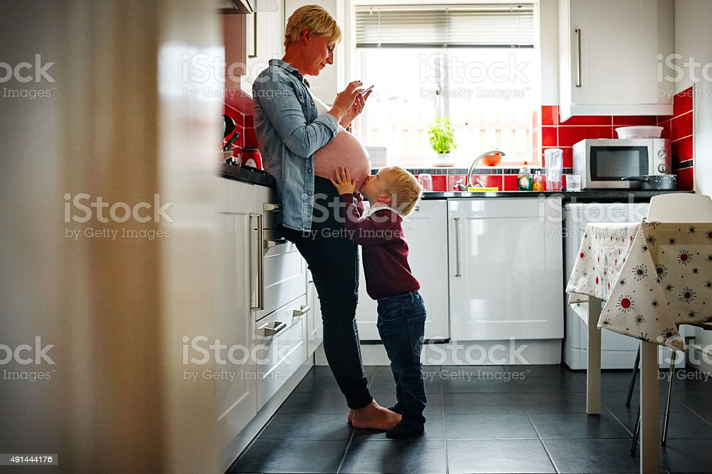 Pregnant woman with her son in the kitchen stock photo