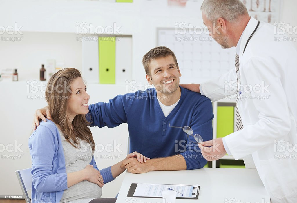 Pregnant woman with husband at doctor's office. royalty-free stock photo