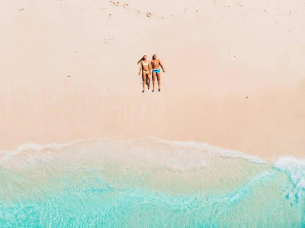 Schwangere Frau mit Mann am tropischen Strand mit blauem Meer. Luftbild – Foto