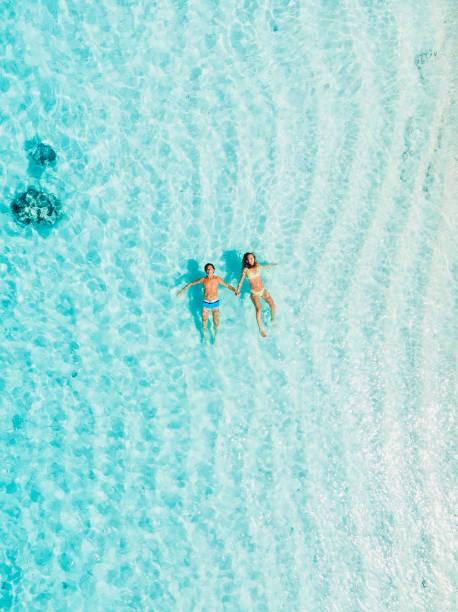 Schwangere Frau mit Mann schwimmen im blauen Meer. Luftbild – Foto
