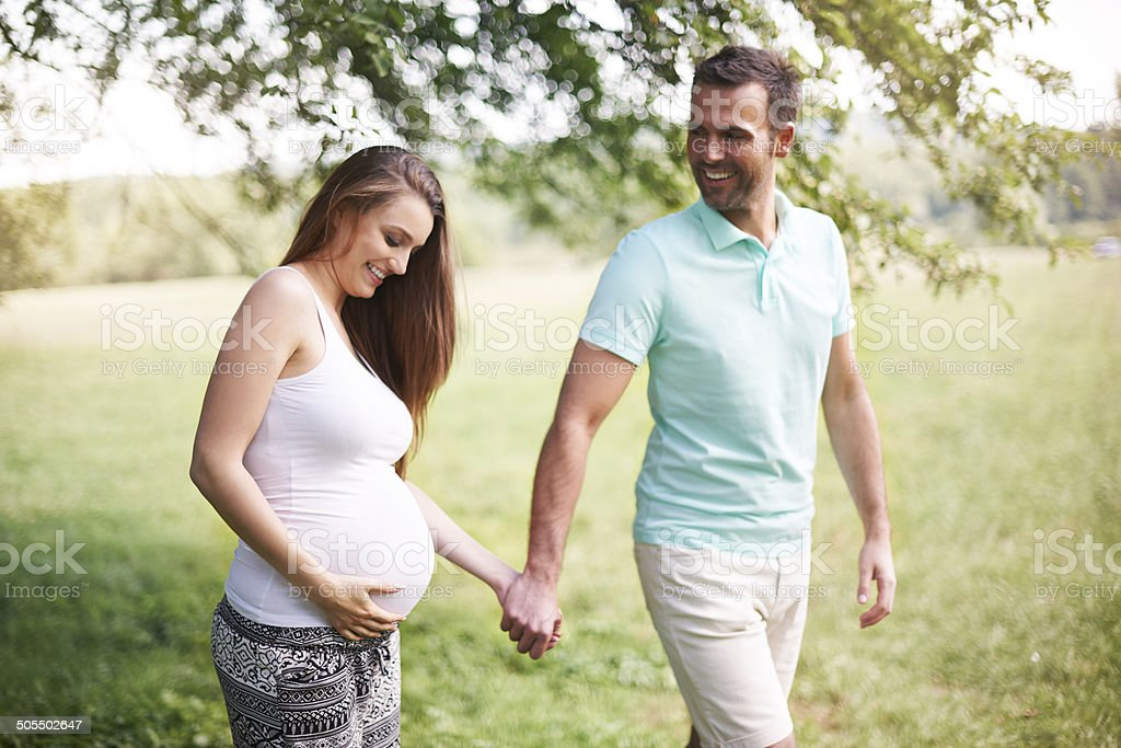 Pregnant woman with husband walking on meadow stock photo