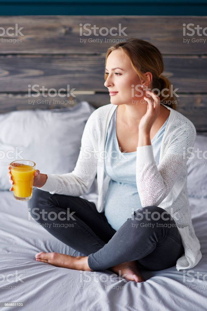 Pregnant woman with orange juice at bedroom royalty-free stock photo